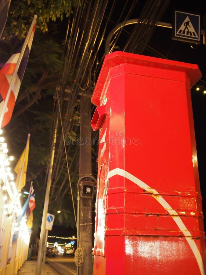 Contenitore rosso di posta sul marciapiede sulle strade pubbliche nell'area urbana immagine stock