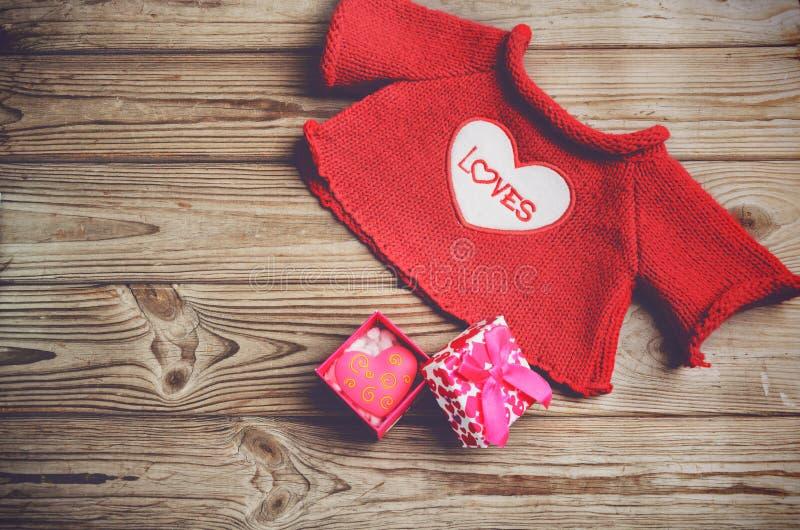 Contenitore rosso sveglio di regalo e di maglione con un cuore su un backgroun di legno fotografia stock libera da diritti
