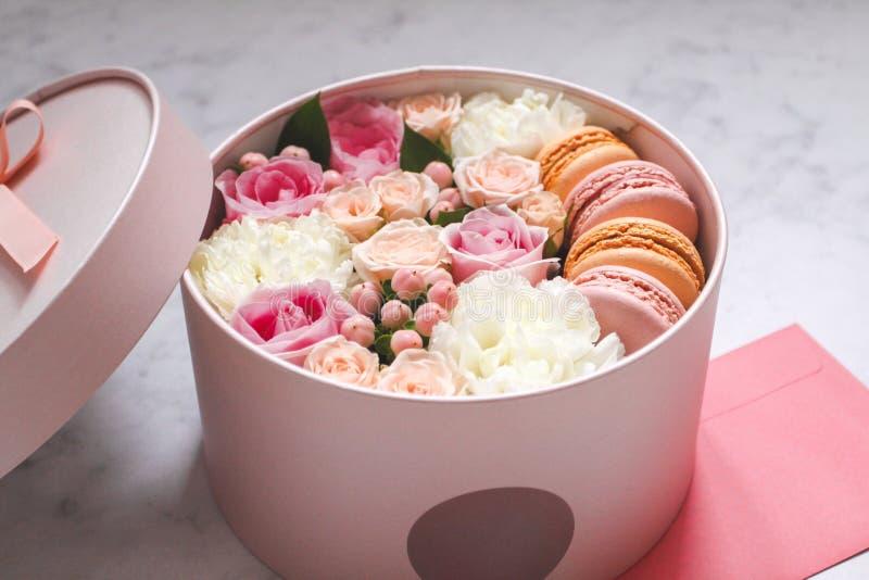 Contenitore rotondo di regalo con i fiori, le rose ed il dolce della mandorla dei maccheroni con la busta rosa sulla tavola fotografie stock