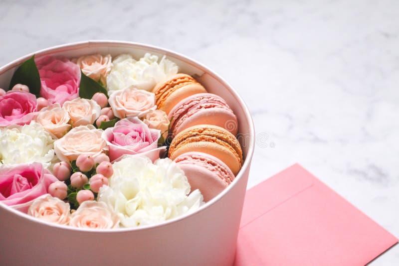 Contenitore rotondo di regalo con i fiori, le rose ed il dolce della mandorla dei maccheroni con la busta rosa sulla tavola immagini stock
