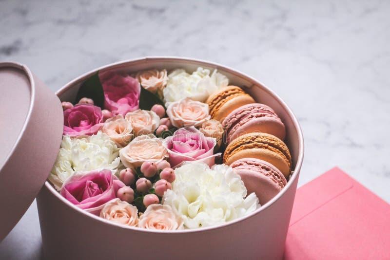 Contenitore rotondo di regalo con i fiori, le rose ed il dolce della mandorla dei maccheroni con la busta rosa sulla tavola immagine stock