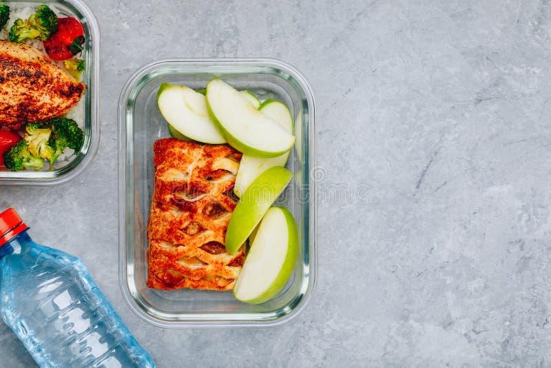 Contenitori arrostiti della preparazione del pasto del pollo con riso, broccoli e pomodori e torta del dessert con la mela verde immagini stock libere da diritti