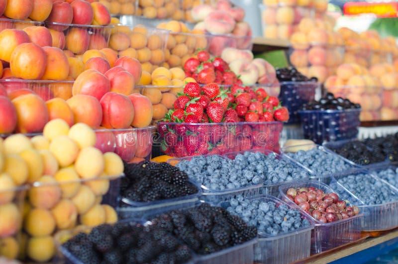 Contenitori con le bacche e la frutta mature differenti al mercato immagini stock