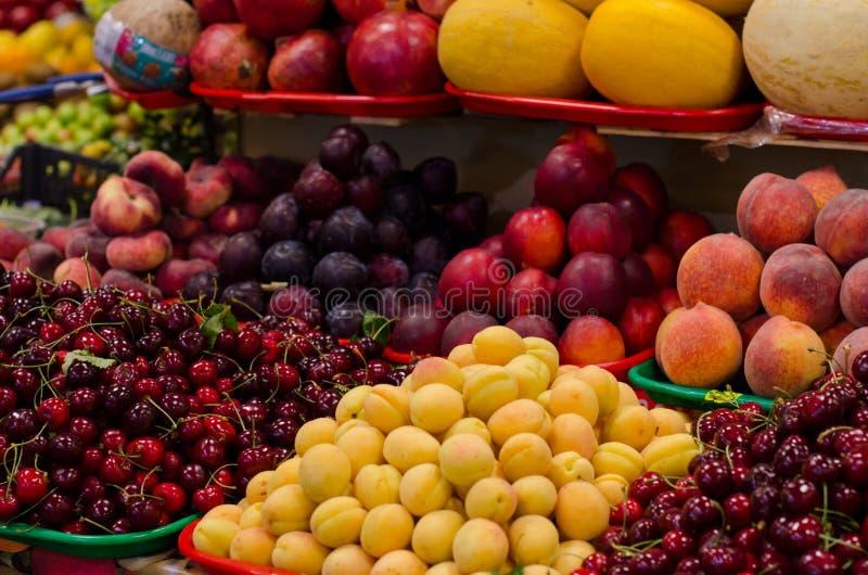 Contenitori con le bacche e la frutta mature differenti al mercato fotografie stock libere da diritti