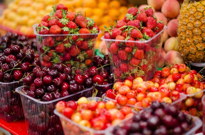 Contenitori con le bacche e la frutta mature differenti al mercato fotografia stock