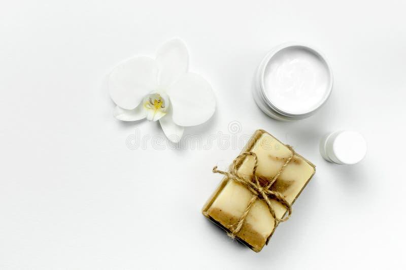 Contenitori cosmetici bianchi della bottiglia, sapone naturale, fiore dell'orchidea sulla disposizione piana bianca di vista supe immagini stock