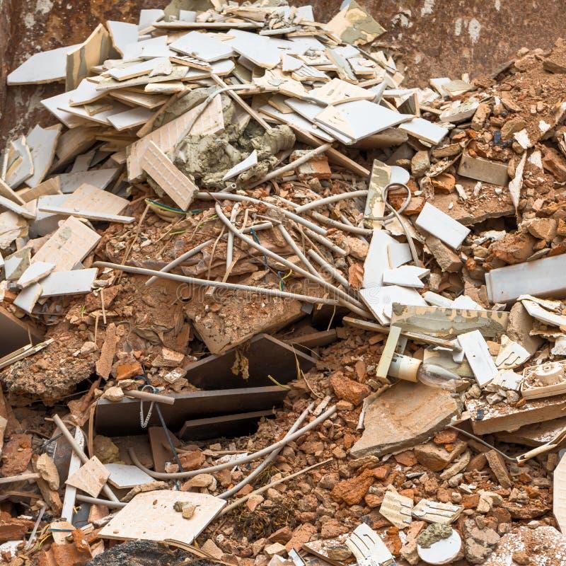 Contenitori d'acciaio con le macerie della costruzione fatte dei cocci di vecchi rifiuti domestici delle mattonelle, dei mattoni, fotografia stock