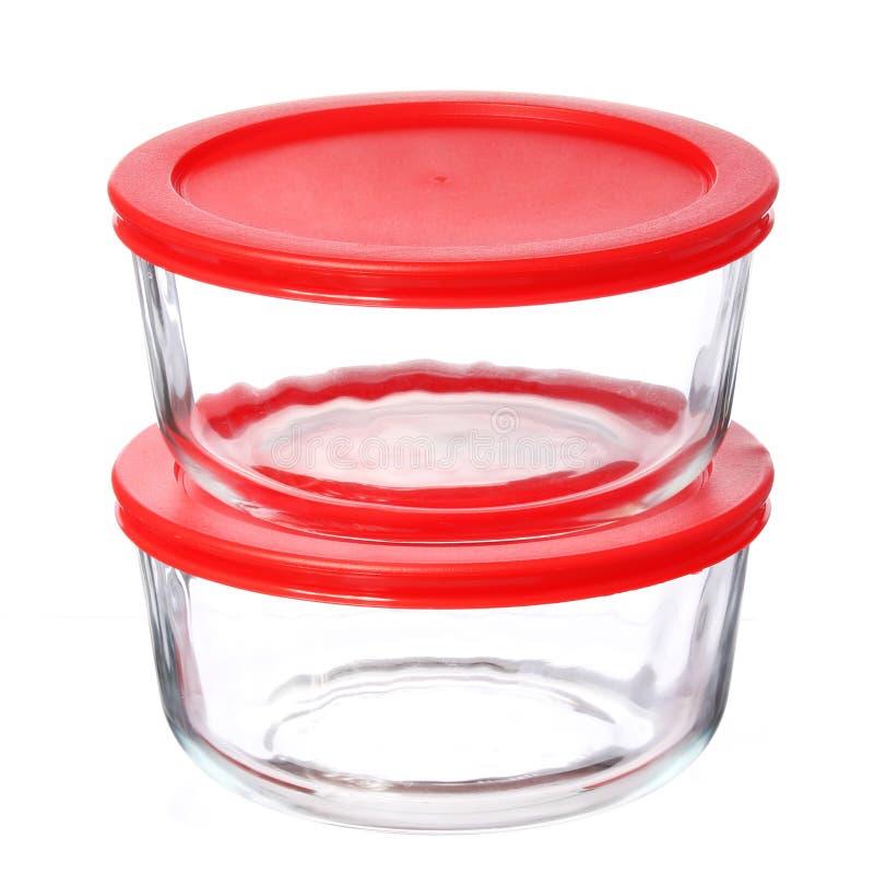 Contenitori di alimento di vetro con i coperchi di plastica rossi isolati su bianco fotografia stock libera da diritti