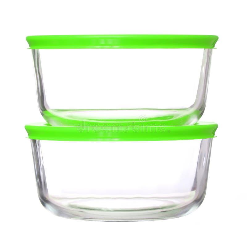 Contenitori di alimento di vetro con i coperchi di plastica verdi su bianco fotografie stock libere da diritti
