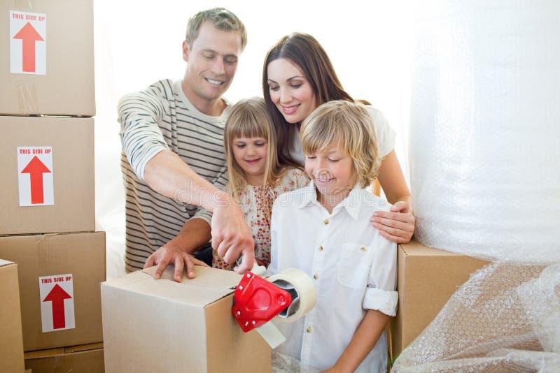 Contenitori di imballaggio allegri della famiglia fotografia stock