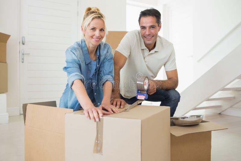 Contenitori di imballaggio sorridenti delle coppie in una nuova casa fotografie stock