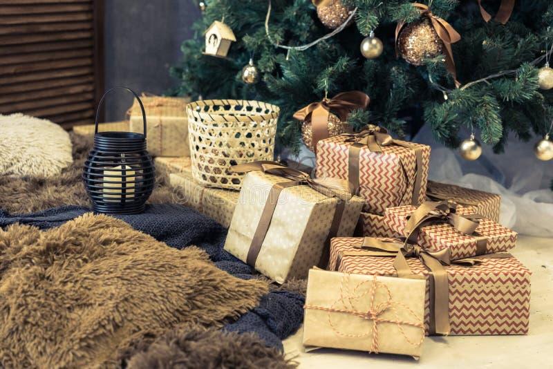 Contenitori di oro con i regali sotto l'albero di Natale immagini stock libere da diritti