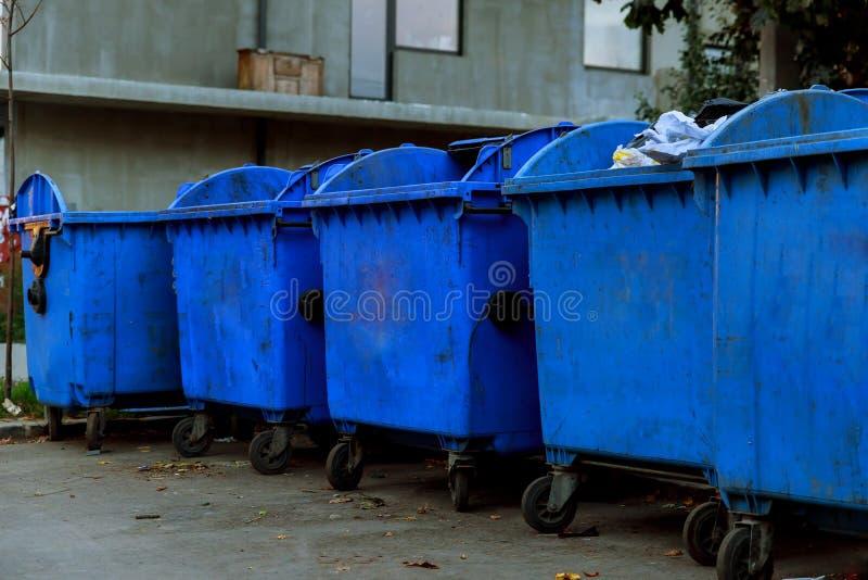 Contenitori di plastica dell'immondizia sulla via che è piena con immondizia fotografie stock