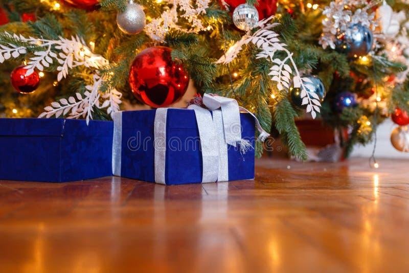 Contenitori di regalo blu di Natale con i nastri bianchi sui precedenti dell'albero di Natale Presente e regali sotto l'albero di fotografie stock