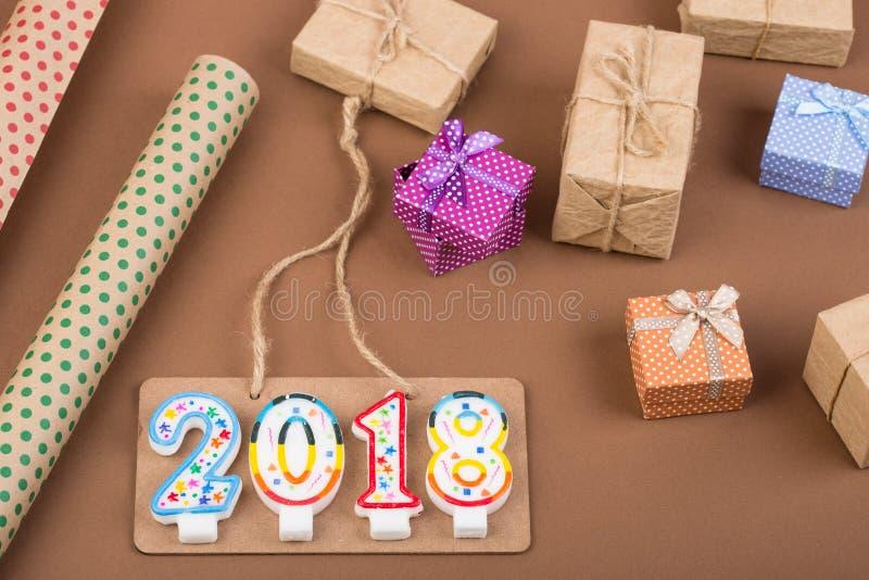 contenitori di regalo, carta da imballaggio, insegna e testo & x22; 2018& x22; fatto delle candele su un fondo della carta marron fotografia stock libera da diritti