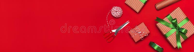 Contenitori di regalo, carta di imballaggio, forbici, nastro su fondo rosso Fondo, congratulazione, spostamento di regalo, Natale immagini stock libere da diritti