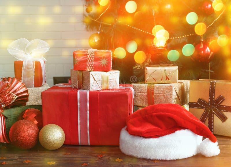 Contenitori di regalo con le perle, i giocattoli ed il cappello di Santa Claus sulla tavola di legno d'annata fotografia stock