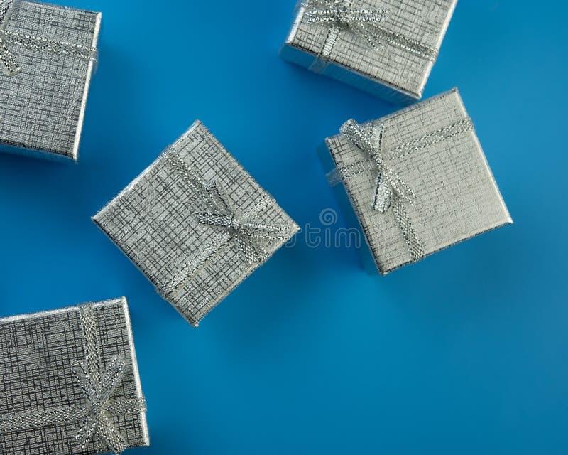 Contenitori di regalo d'argento festivi su un fondo blu fotografia stock