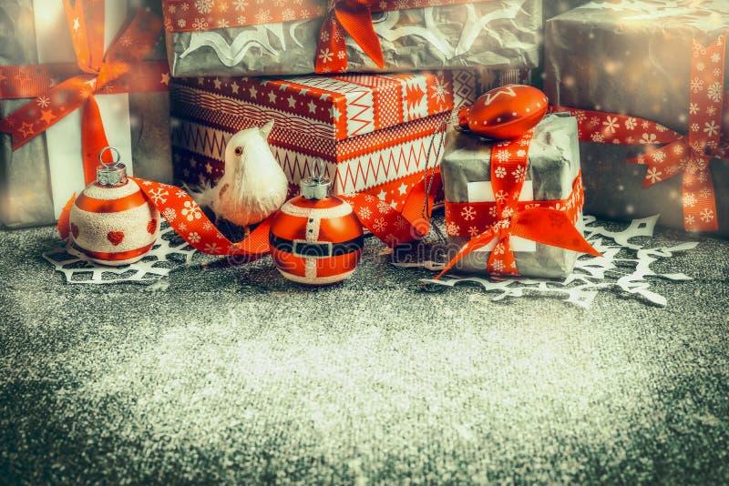 Contenitori di regalo di Natale con i nastri rossi e decorazione su fondo rustico fotografie stock libere da diritti