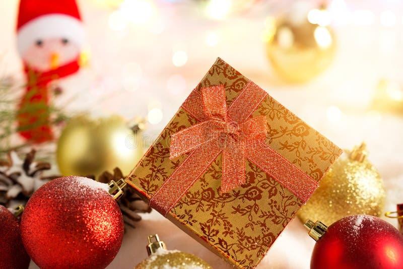 Contenitori di regalo di Natale dell'oro con il pupazzo di neve e la bagattella su neve nell'accensione variopinta immagine stock