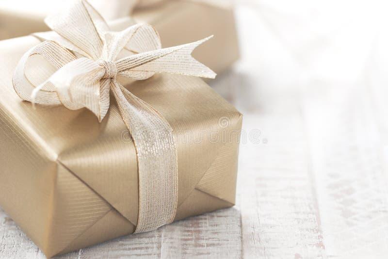 Contenitori di regalo dorati con il bei nastro ed arco su uno stinco luminoso fotografia stock libera da diritti