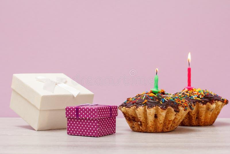 Contenitori di regalo e muffin di compleanno con le candele festive di combustione su fondo lilla fotografie stock libere da diritti