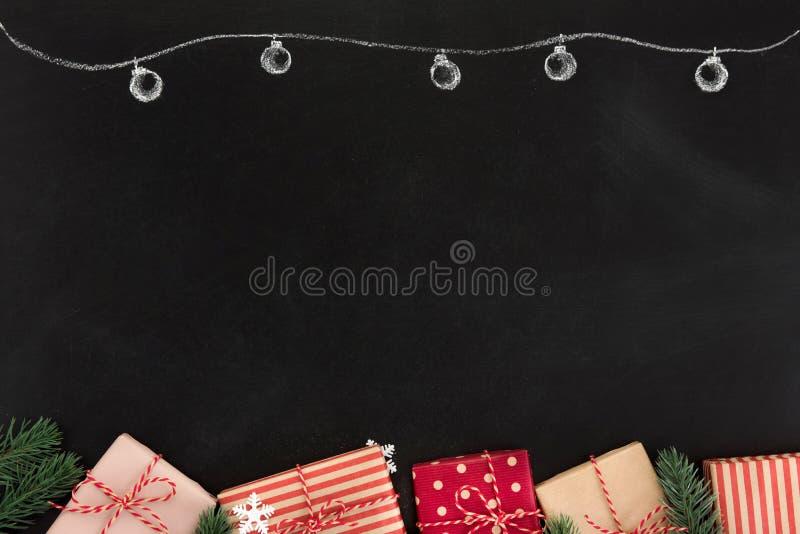 Contenitori di regalo ed ornamenti di Natale, progettazione del confine, sulla lavagna fotografia stock