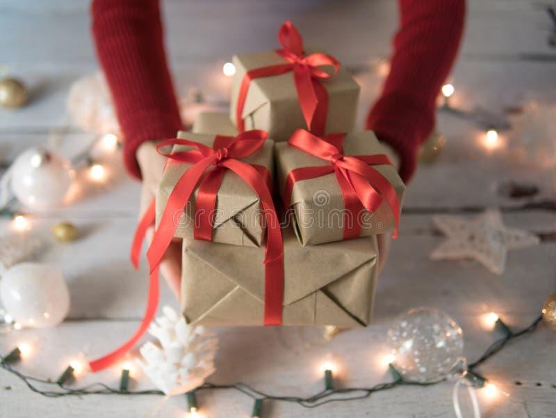 Contenitori di regalo femminili di Natale della tenuta sopra il Natale ornamento e luci fotografie stock libere da diritti