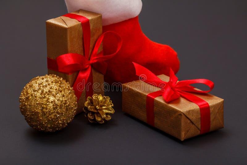 Contenitori di regalo, lo stivale di Santa, palla di natale e cono su fondo nero fotografia stock