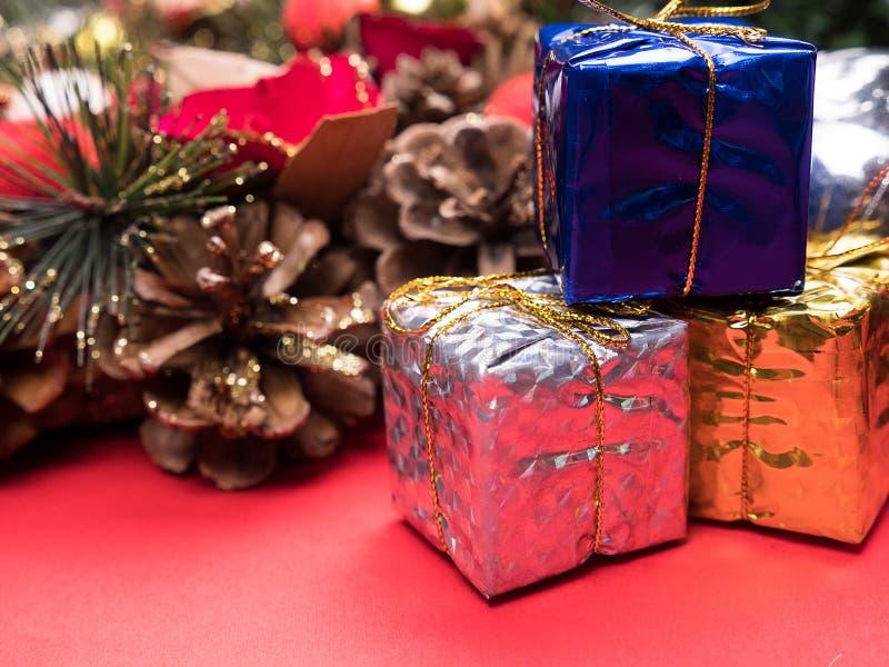 Contenitori di regalo di Natale avvolti nei colori differenti sotto l'albero di Natale su fondo rosso fotografia stock