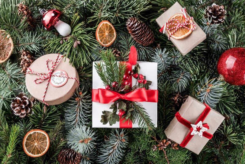 Contenitori di regalo di Natale con la decorazione rossa, pigne sul fondo dei rami di albero Tema di natale, concetto del nuovo a immagine stock libera da diritti