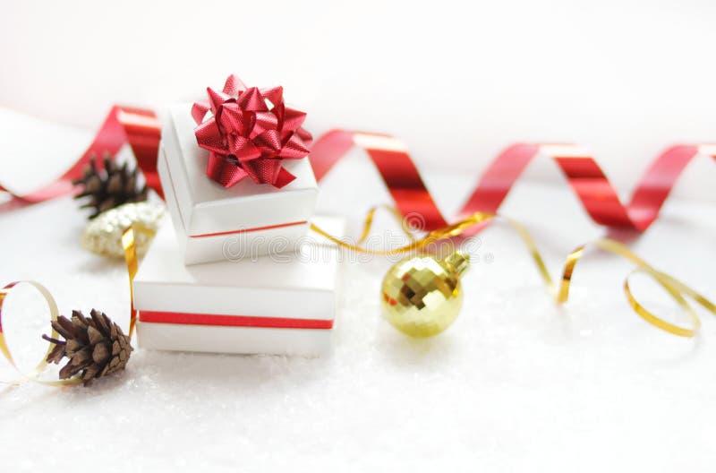 Contenitori di regalo di Natale con un arco rosso, accanto alla palla di Natale, nastro rosso, coni su un fondo bianco con neve immagini stock
