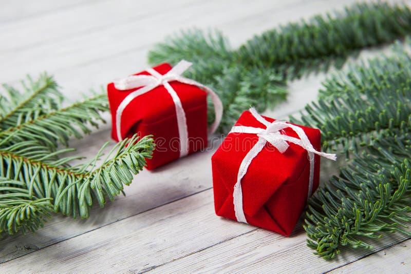 Contenitori di regalo di Natale e rami dell'abete su un fondo di legno, il concetto della celebrazione del nuovo anno fotografie stock