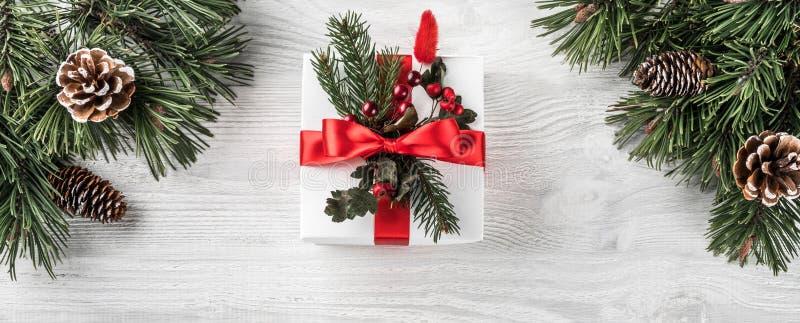Contenitori di regalo di Natale su fondo di legno bianco con i contenitori di regalo di brancheChristmas dell'abete su fondo di l immagine stock libera da diritti
