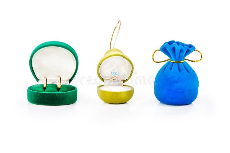 Contenitori di regalo per gioielli con le fedi nuziali dell'oro e l'anello di fidanzamento dell'oro con topazio blu immagine stock