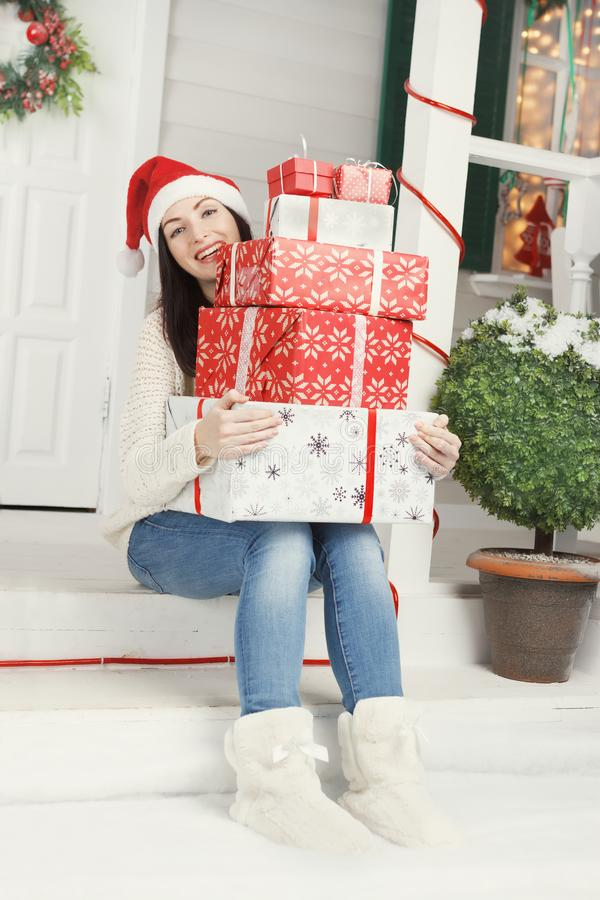 Contenitori di regalo di risata di Natale della tenuta della giovane donna fotografia stock libera da diritti