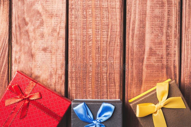 Contenitori di regalo variopinti su fondo di legno scuro fotografie stock libere da diritti