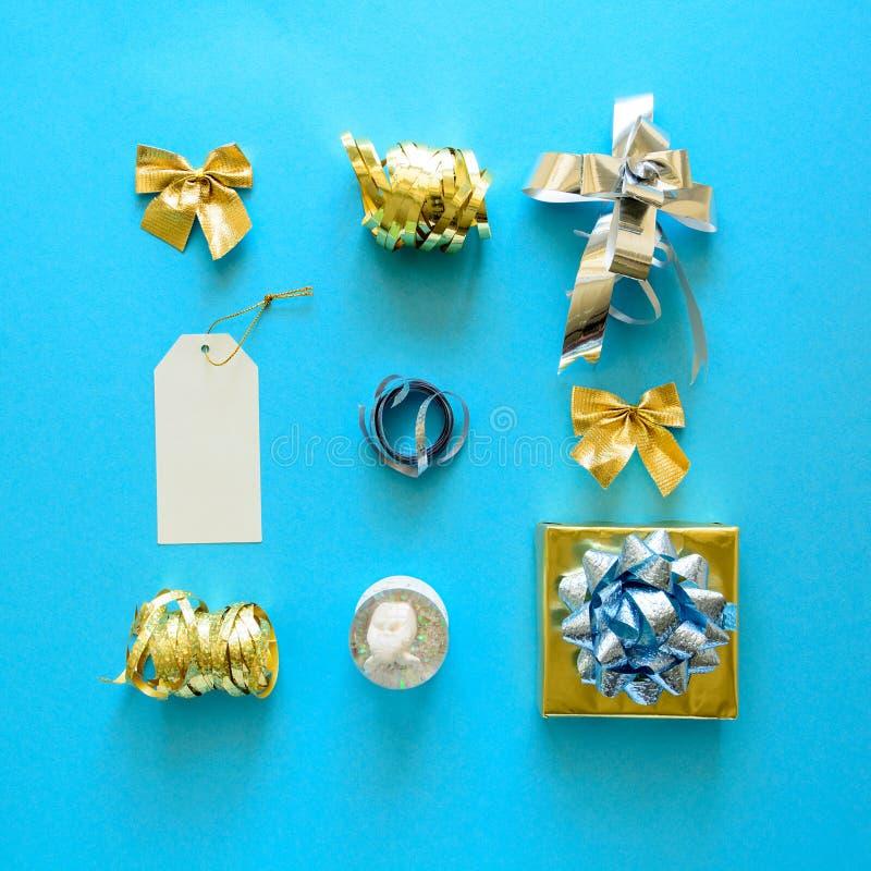Contenitori e decorazioni di regalo dorati e d'argento di Natale su fondo blu Disposizione piana Vista superiore fotografia stock libera da diritti