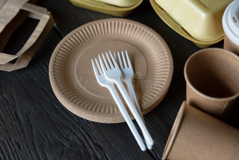 Contenitori eliminabili e stoviglie di alimento asportabile su fondo di legno scuro Utensile amichevole della cucina della natura immagine stock