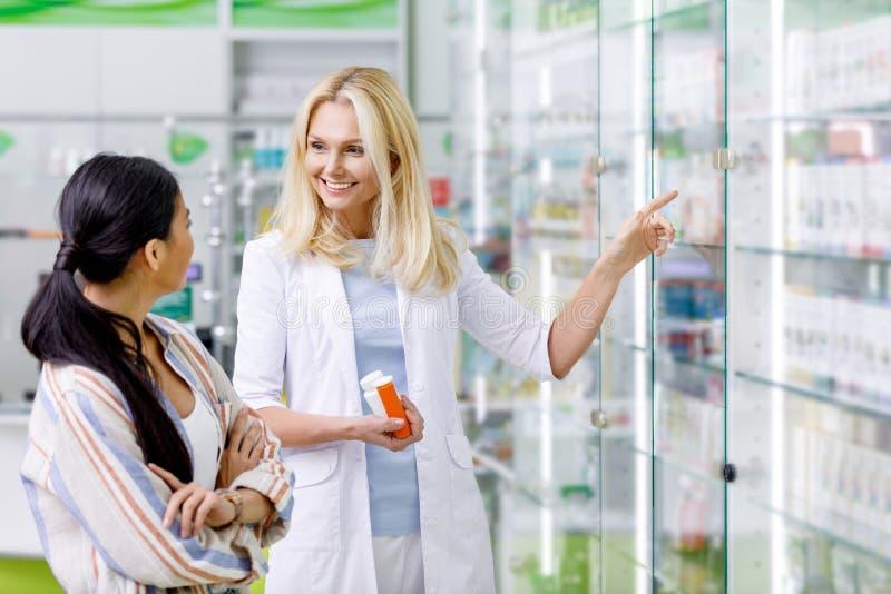 contenitori sorridenti della tenuta del farmacista con il farmaco ed il cliente consultantesi fotografie stock libere da diritti