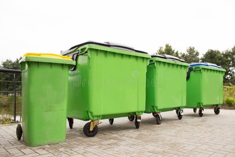 Contenitori verdi dell'immondizia in una fila fotografie stock