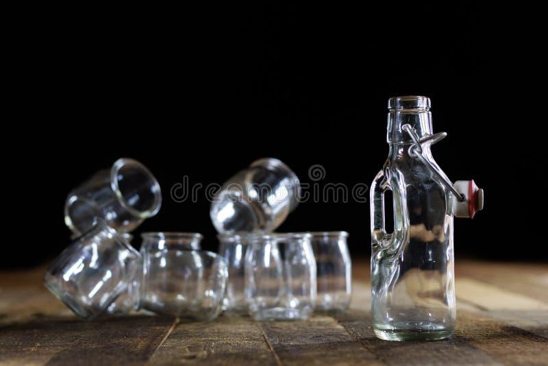 Contenitori vuoti di vetro su una tavola di legno Barattoli, bottiglia immagine stock libera da diritti