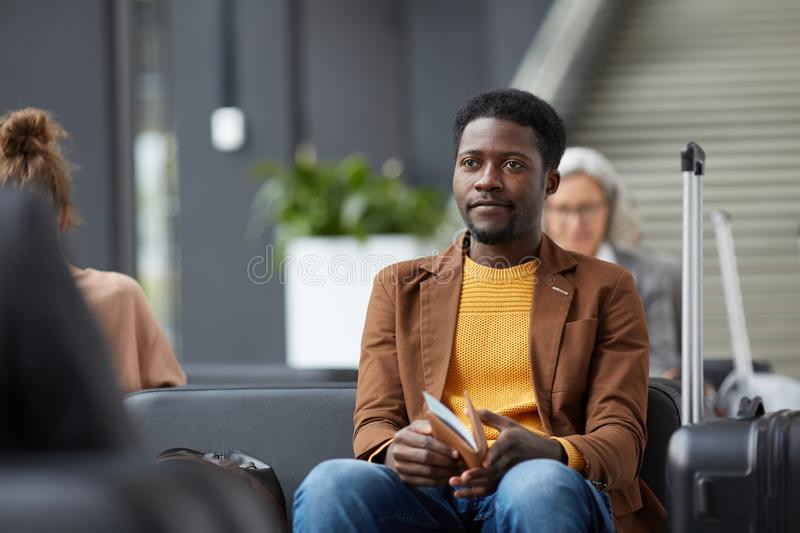 Content Afro-American guy with passport. Content Afro-American guy with beard sitting in airport waiting area and holding passport and boarding pass stock photos