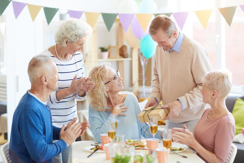 Giving birthday present to woman from all friends stock photos