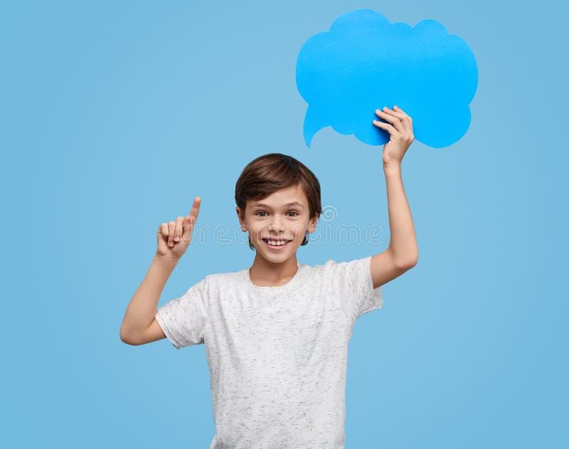 Content boy having idea while holding speech bubble stock images