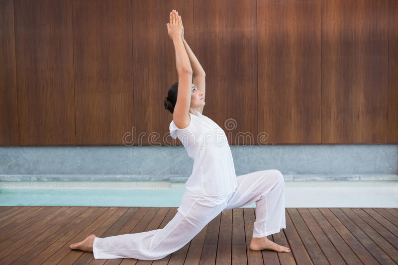 Content brunette in white doing tai chi. In health spa stock photography