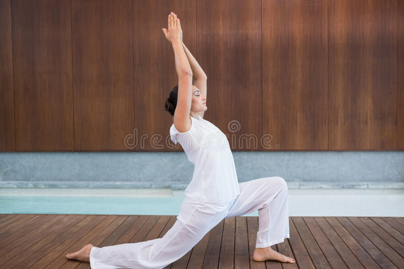 Content brunette in white doing tai chi. In health spa royalty free stock image