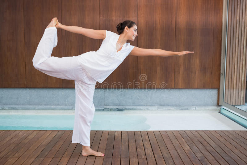 Content brunette in white in the shiva posture. In health spa royalty free stock image