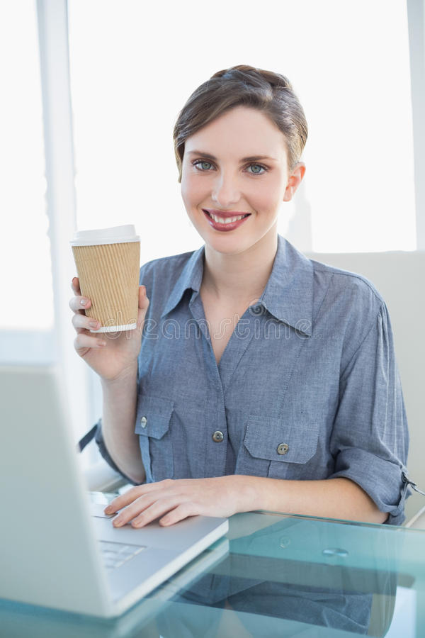 Content businesswoman showing disposable cup sitting at her desk stock photos