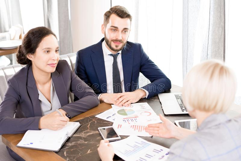 Team of financial advisors meeting with client. Content confident team of financial experts in formalwear sitting at table and talking to customer at meeting royalty free stock photography